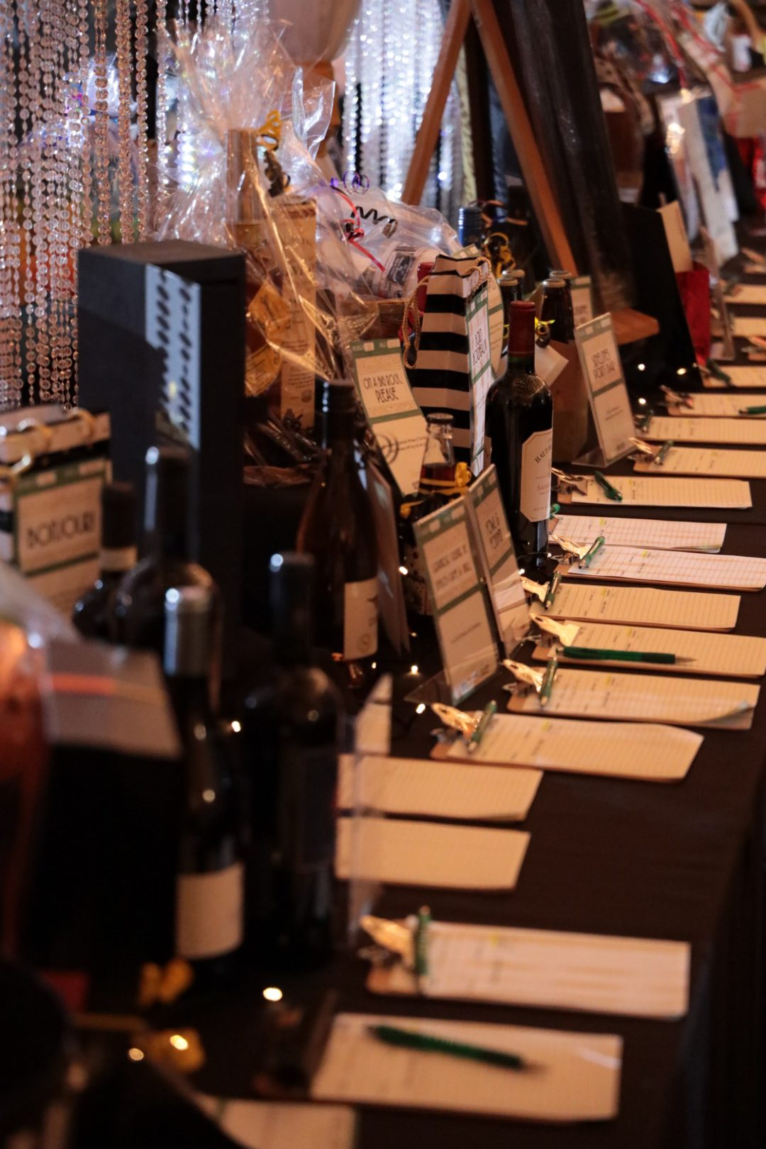 Silent auction items with bidding forms across a table