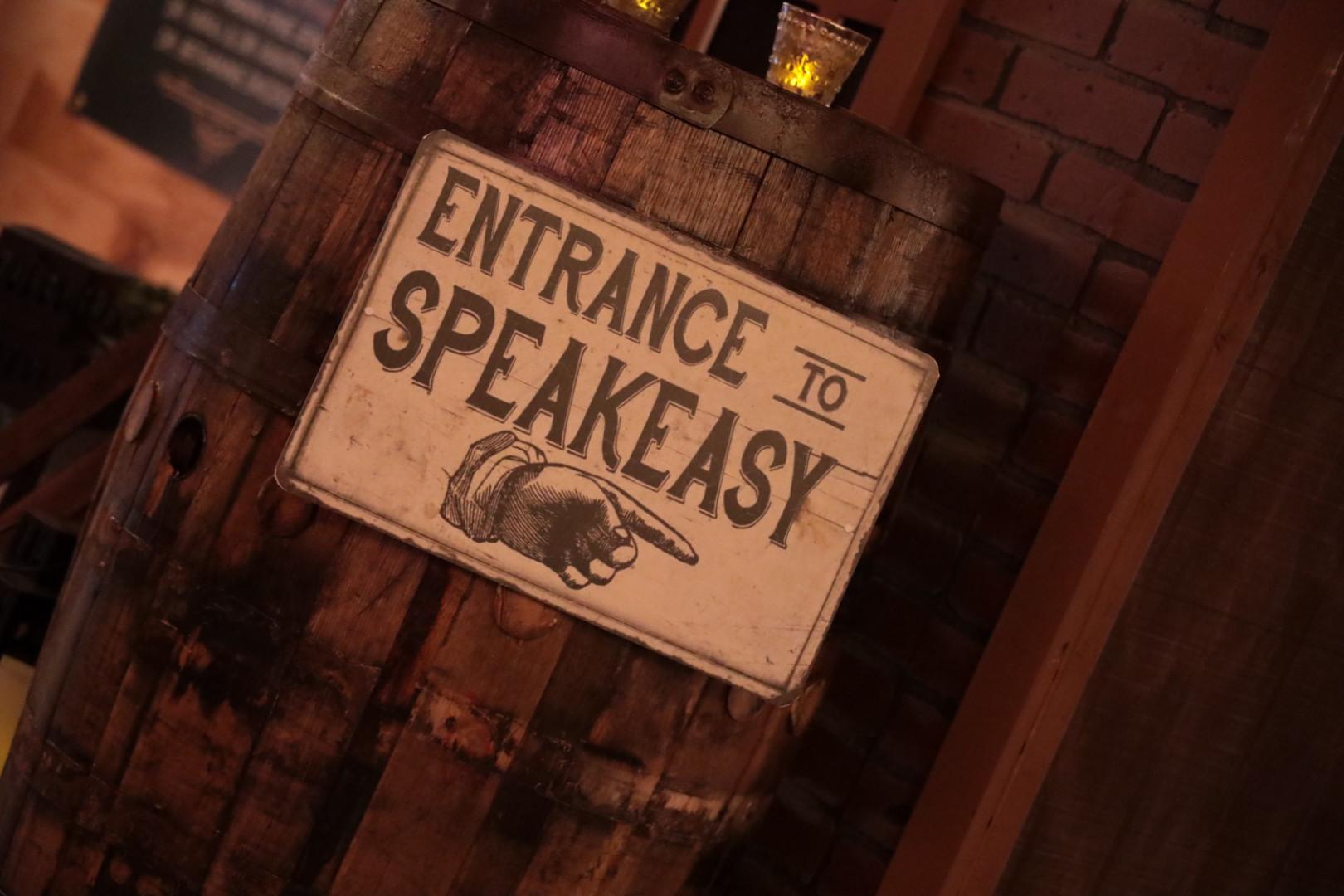 Entrance to speakeasy sign on a wooden bourbon barrel