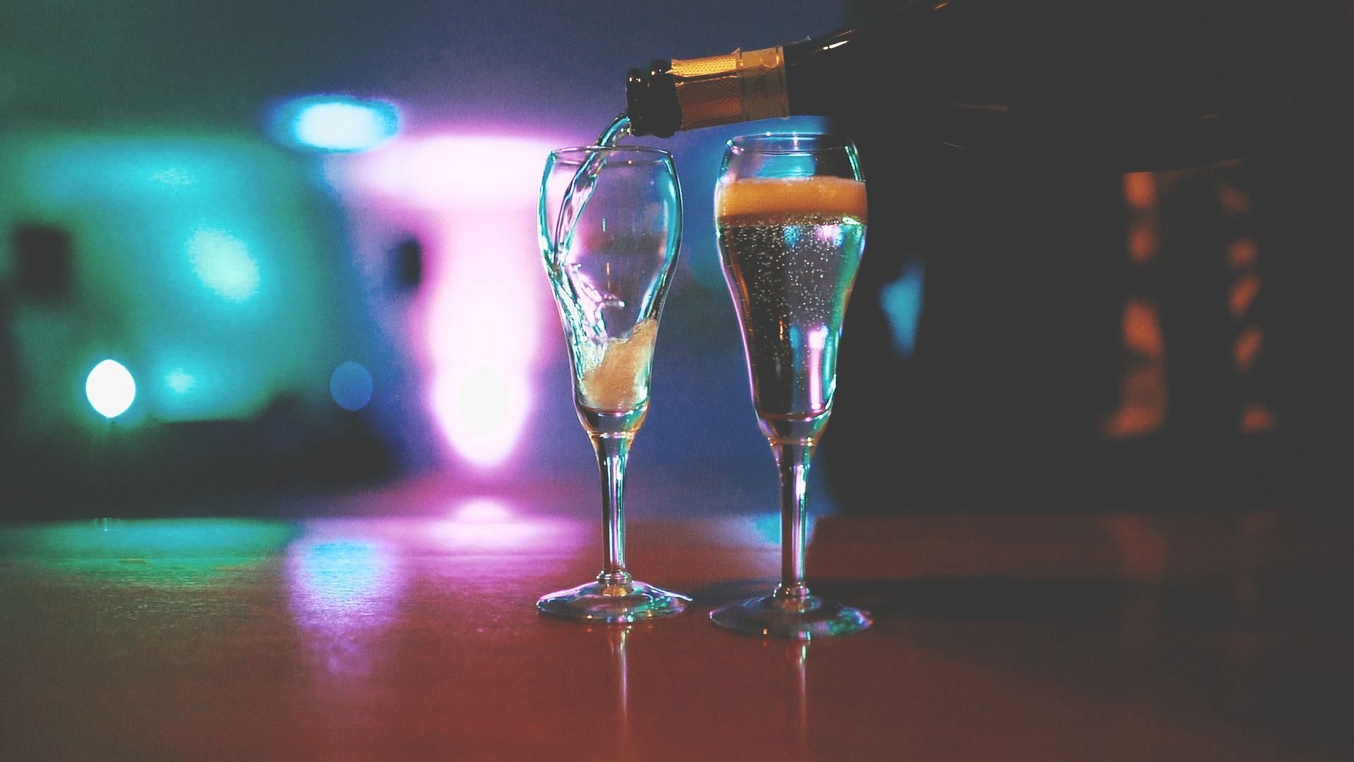 Two champagne glasses being filled with up-lit background