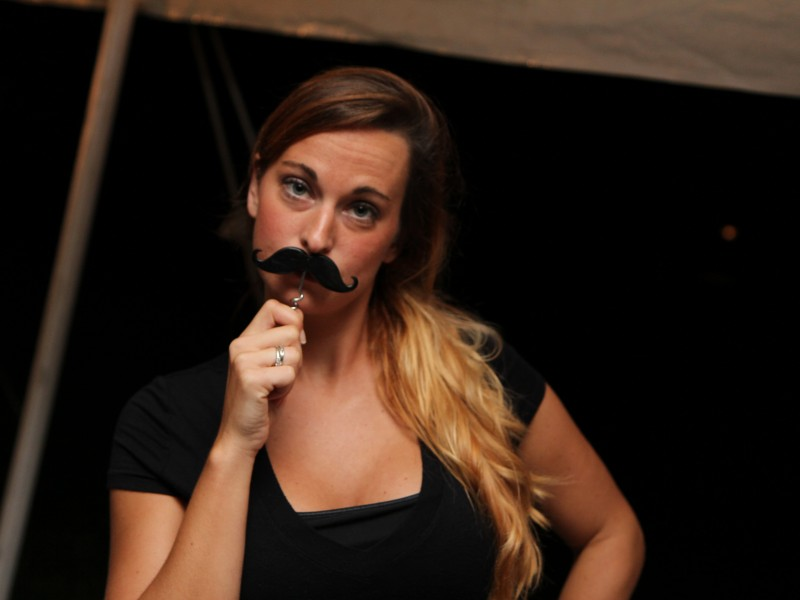 Fun, attractive female bartender with a mustache bottle opener enjoying her time bartending at a mobile bartending event