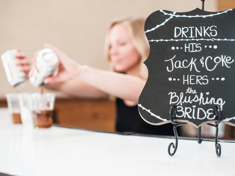 Chalkboard specialty cocktail menu with a his and hers drink selection with bartender in background