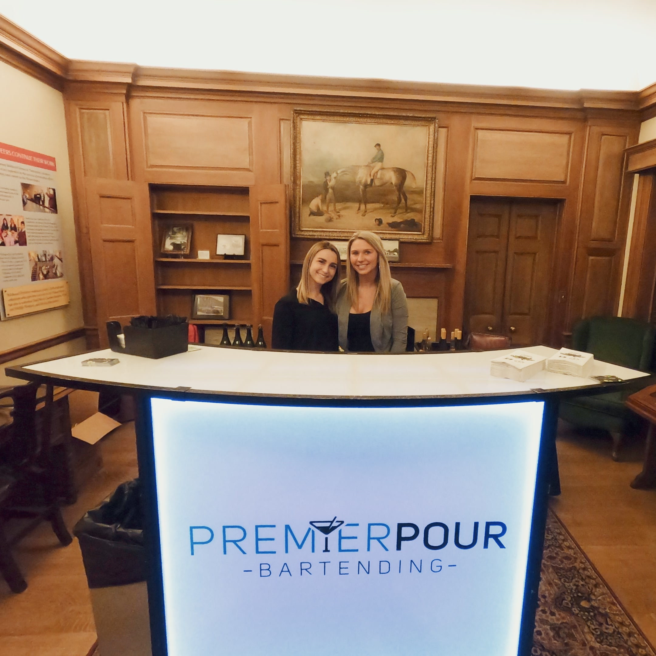 Two female bartenders behind white Premier Pour Bartending portable bar