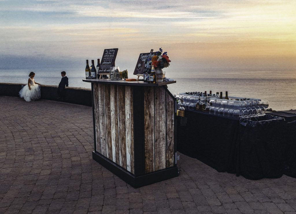 Portable bar with wood look on brick patio overlooking a lake sunset