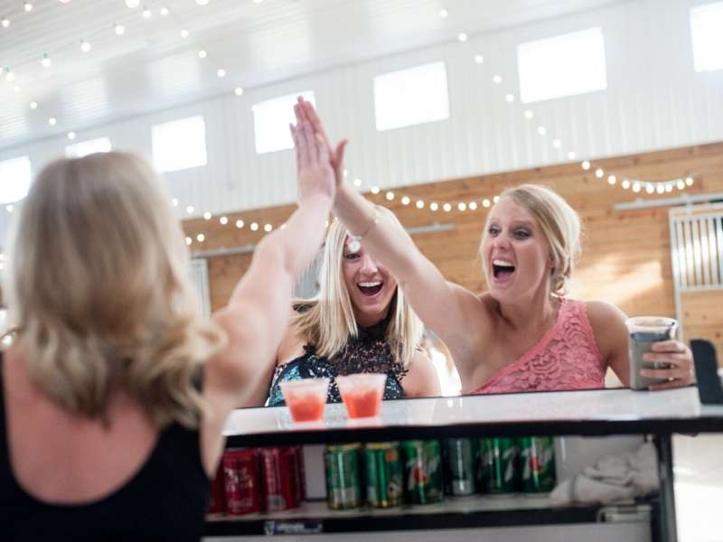 Female bartender giving a high five to wedding guests at The Stables in Whitehouse, OH
