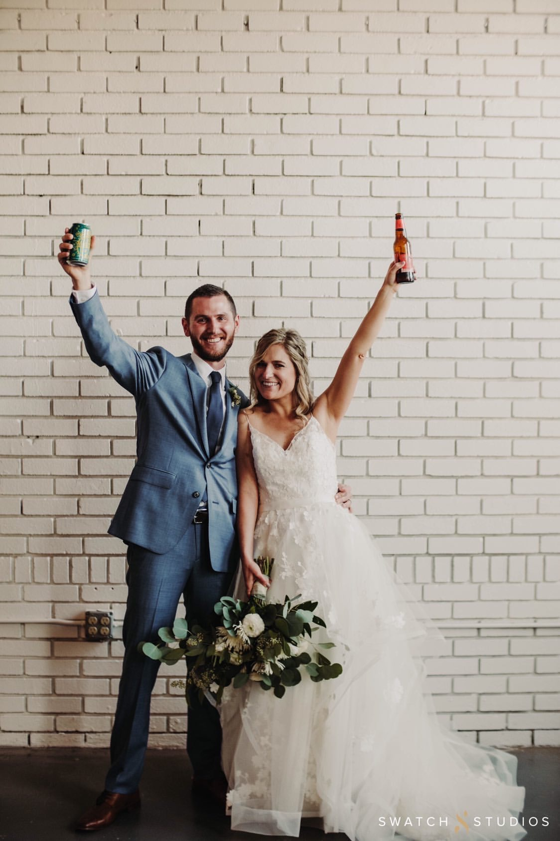 Bride and groom raising glasses to toast in front of a white brick wall at The Venues in Downtown Toledo