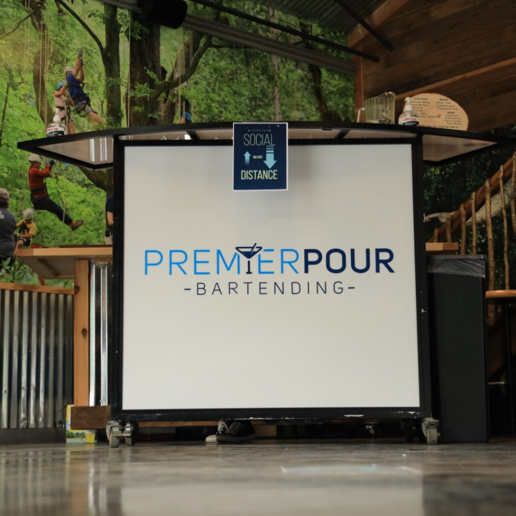 Premier Pour Bartending white mobile bar with logo set up for an event with Metroparks Toledo.
