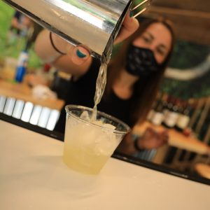 Female bartender with custom Premier Pour Bartending facemask pouring a Bee's Knees cocktail from a stainless steel shaker.