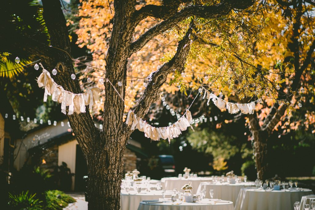 Backyard wedding with hanging lights above tables decorated for a wedding reception.