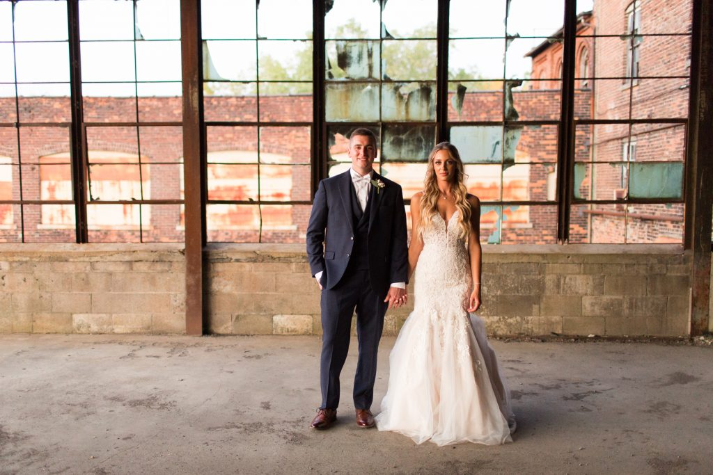 Macy and Ryan Terry posing in their wedding attire at The Venues event space in Downtown Toledo.