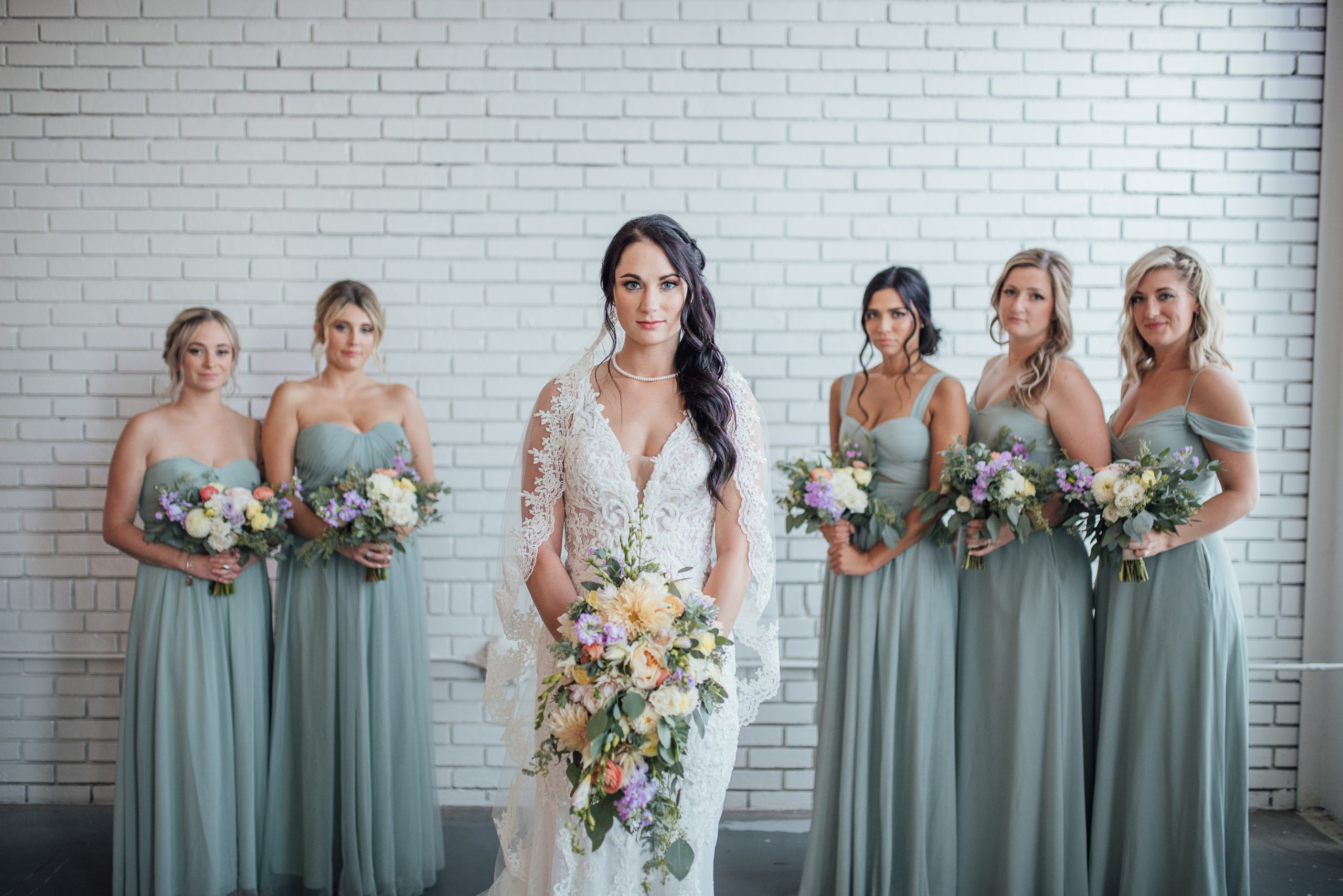 Danielle and her bridesmaids in front of the brick wall at The Venues Toledo.